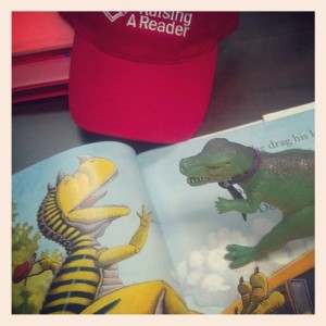 T-Jag found a dinosaur book while visiting the folks at nonprofit Raising A Reader.